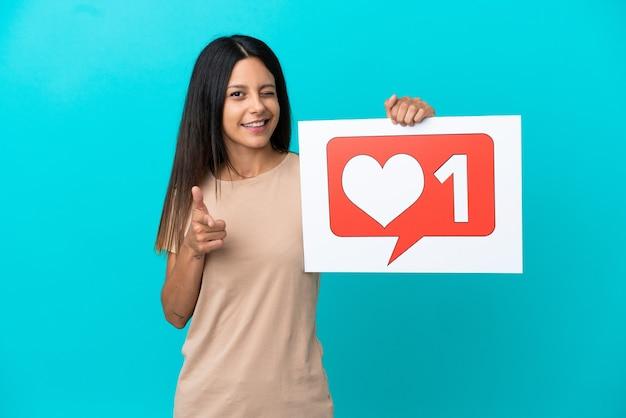 Jonge vrouw over geïsoleerde achtergrond met een bordje met like-pictogram en naar voren wijzend