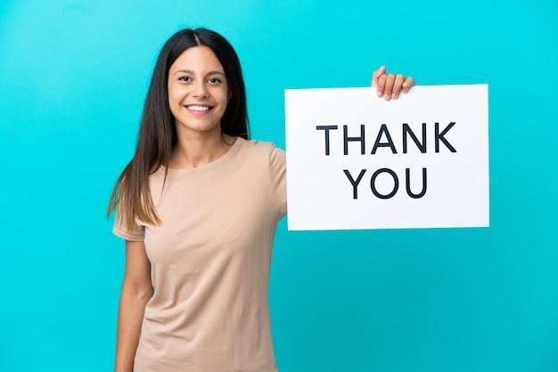 Jonge vrouw over geïsoleerde achtergrond met een bordje met tekst dank u met gelukkige uitdrukking