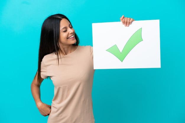 Jonge vrouw over geïsoleerde achtergrond met een bordje met tekst groen vinkje pictogram met gelukkige expressie