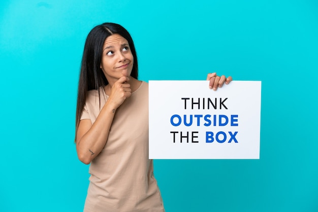Jonge vrouw over geïsoleerde achtergrond met een bordje met tekst think outside the box en denken