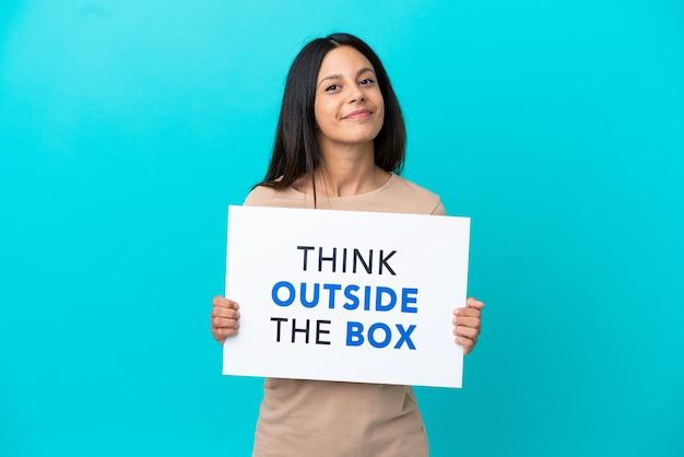 Jonge vrouw over geïsoleerde achtergrond met een bordje met tekst think outside the box