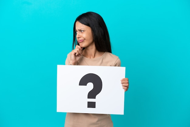 Jonge vrouw over geïsoleerde achtergrond met een bordje met vraagtekensymbool en denken