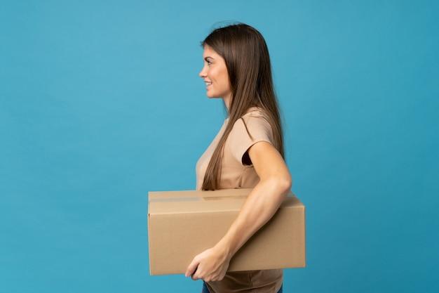 Jonge vrouw over geïsoleerde blauw die een doos houdt om het naar een andere plaats in zijpositie te verplaatsen
