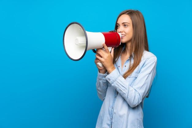 Jonge vrouw over geïsoleerde blauwe achtergrond die door een megafoon schreeuwt