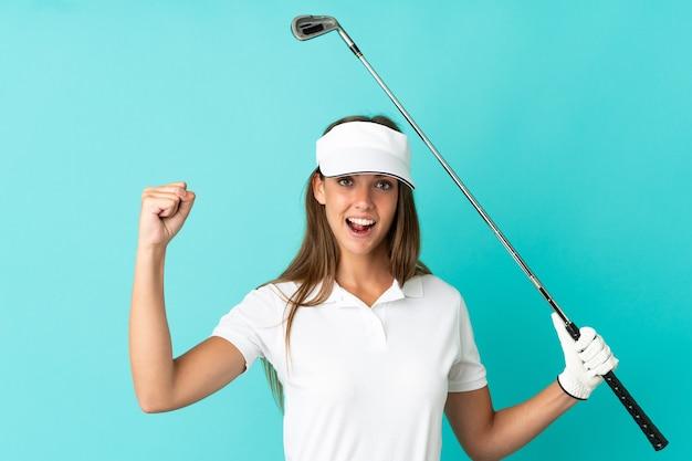 Jonge vrouw over geïsoleerde blauwe achtergrond die golf speelt en een overwinning viert