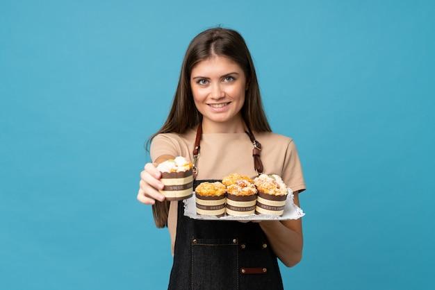 Jonge vrouw over geïsoleerde blauwe achtergrond die minicakes houden en het aanbieden