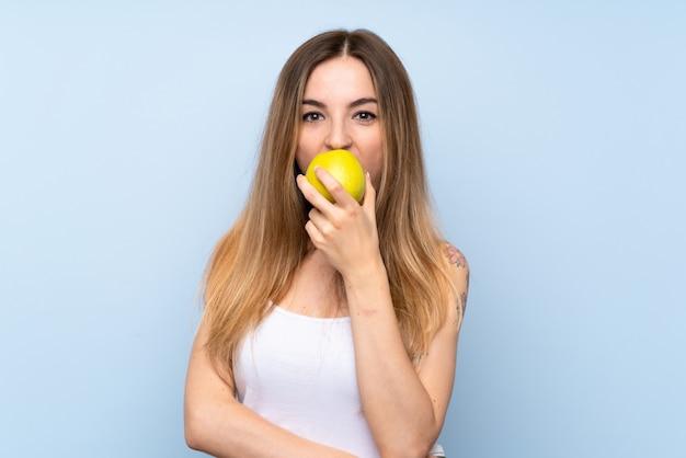 Jonge vrouw over geïsoleerde blauwe achtergrond met een appel