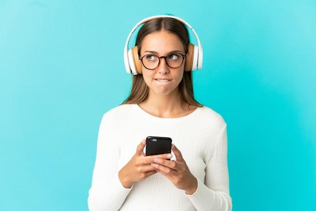 Jonge vrouw over geïsoleerde blauwe achtergrond muziek luisteren met een gsm en denken