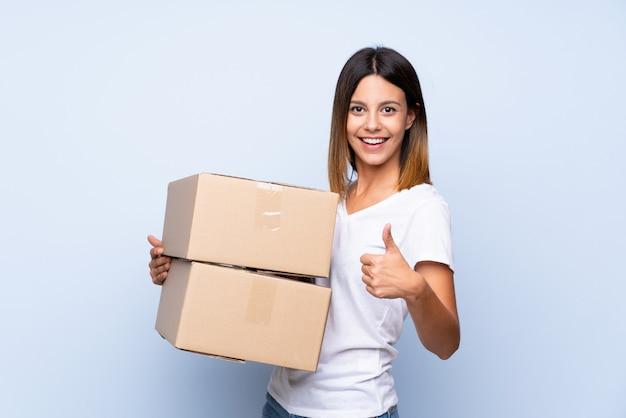 Jonge vrouw over geïsoleerde blauwe muur die een doos houdt om het naar een andere plaats met omhoog duim te verplaatsen