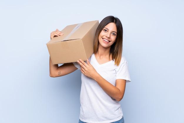 Jonge vrouw over geïsoleerde blauwe muur die een doos houdt om het naar een andere plaats te verplaatsen