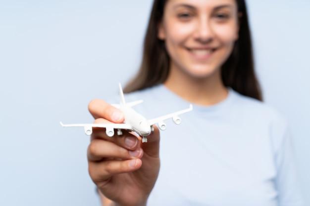 Jonge vrouw over geïsoleerde blauwe muur die een stuk speelgoed vliegtuig houdt