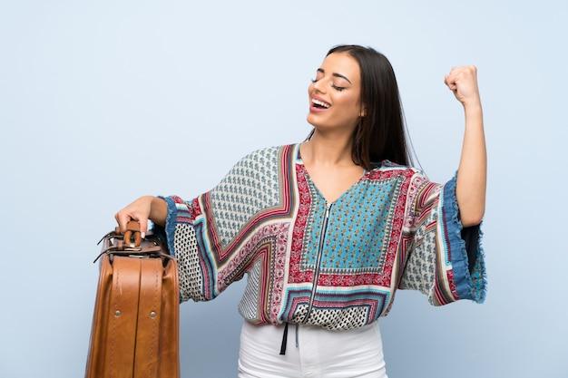Jonge vrouw over geïsoleerde blauwe muur die een uitstekende aktentas houdt