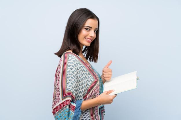 Jonge vrouw over geïsoleerde blauwe muur die en een boek houdt leest