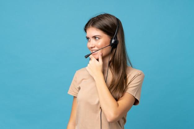 Jonge vrouw over geïsoleerde blauwe muur die met hoofdtelefoon werkt die kant kijkt