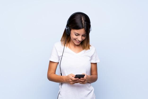 Jonge vrouw over geïsoleerde blauwe muur die mobiel met hoofdtelefoons gebruikt