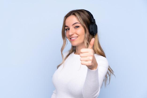Jonge vrouw over geïsoleerde blauwe muur het luisteren muziek en met omhoog duim