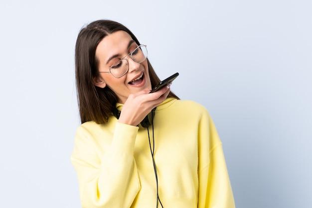 Jonge vrouw over geïsoleerde blauwe muur het luisteren muziek met mobiel en zingend