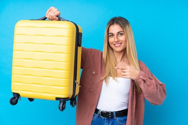 Jonge vrouw over geïsoleerde blauwe muur in vakantie met reiskoffer