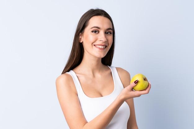 Jonge vrouw over geïsoleerde blauwe muur met een appel