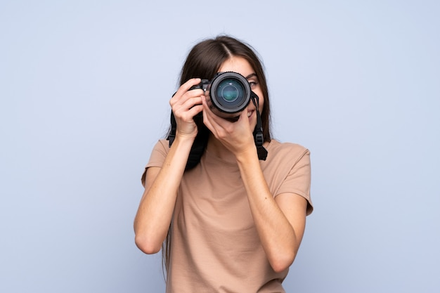 Jonge vrouw over geïsoleerde blauwe muur met een professionele camera