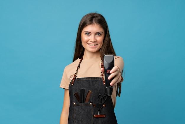 Jonge vrouw over geïsoleerde blauwe muur met kapper of kapper kleding en haar snijmachine te houden