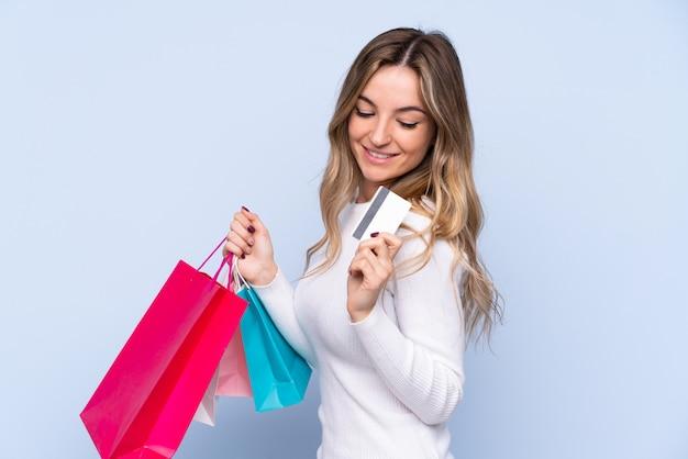 Jonge vrouw over geïsoleerde blauwe muurholding het winkelen zakken en een creditcard