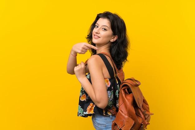 Jonge vrouw over geïsoleerde gele achtergrond met rugzak