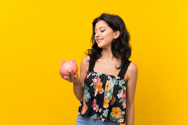 Jonge vrouw over geïsoleerde gele muur die een grote spaarpot houdt