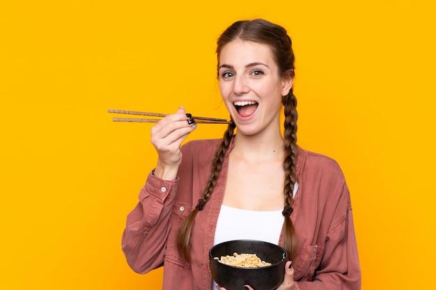 Jonge vrouw over geïsoleerde gele muur die een kom van noedels met eetstokjes houdt