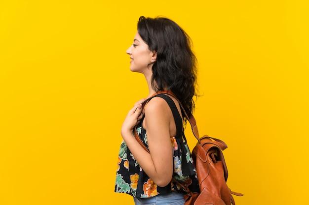Jonge vrouw over geïsoleerde gele muur met rugzak