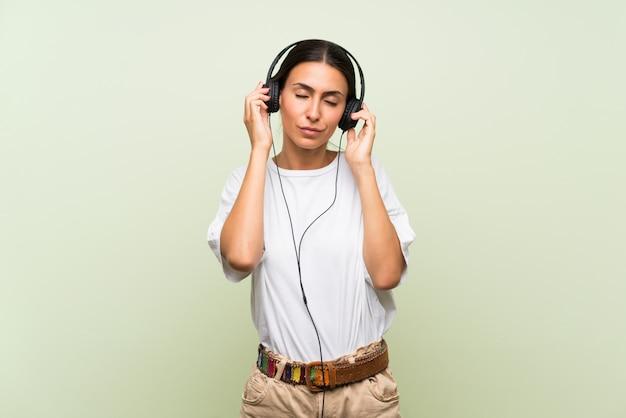 Jonge vrouw over geïsoleerde groene muur die aan muziek met hoofdtelefoons luistert