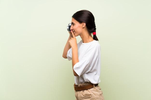 Jonge vrouw over geïsoleerde groene muur die een camera houdt