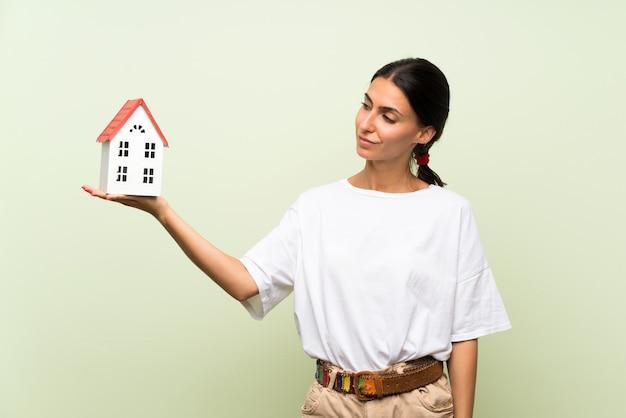 Jonge vrouw over geïsoleerde groene muur die een klein huis houdt