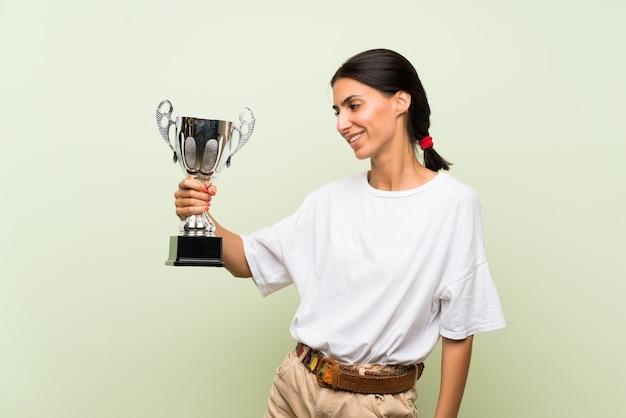 Jonge vrouw over geïsoleerde groene muur die een trofee houdt