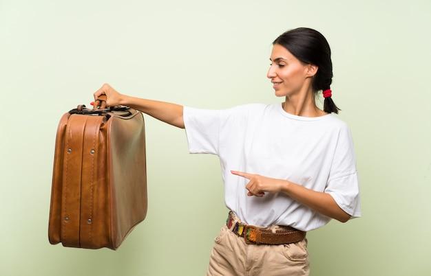 Jonge vrouw over geïsoleerde groene muur die een uitstekende aktentas houdt