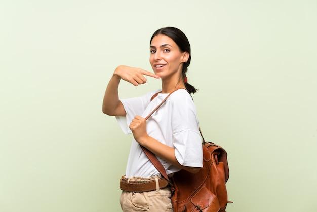 Jonge vrouw over geïsoleerde groene muur met rugzak