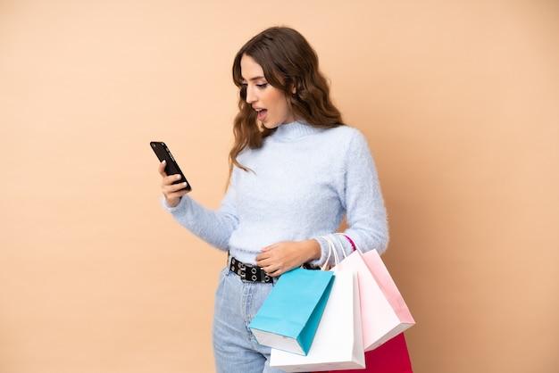 Jonge vrouw over geïsoleerde muur holding boodschappentassen en het schrijven van een bericht met haar mobiele telefoon naar een vriend