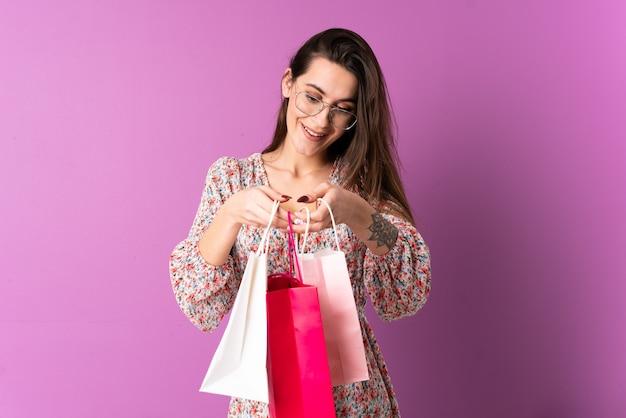 Jonge vrouw over geïsoleerde paarse muur boodschappentassen houden en kijken erin