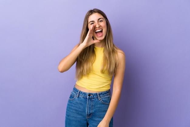 Jonge vrouw over geïsoleerde purpere muur die met wijd open mond schreeuwen
