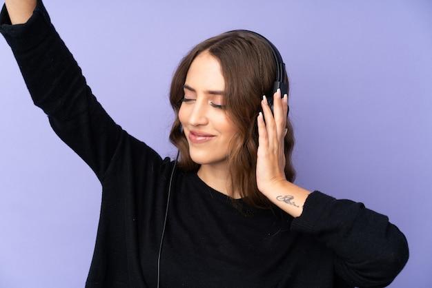 Jonge vrouw over geïsoleerde purpere muur het luisteren muziek en het dansen