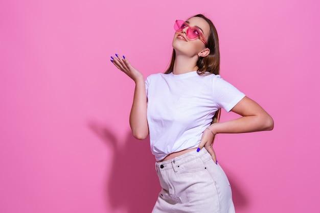 Jonge vrouw over geïsoleerde roze achtergrond met bril