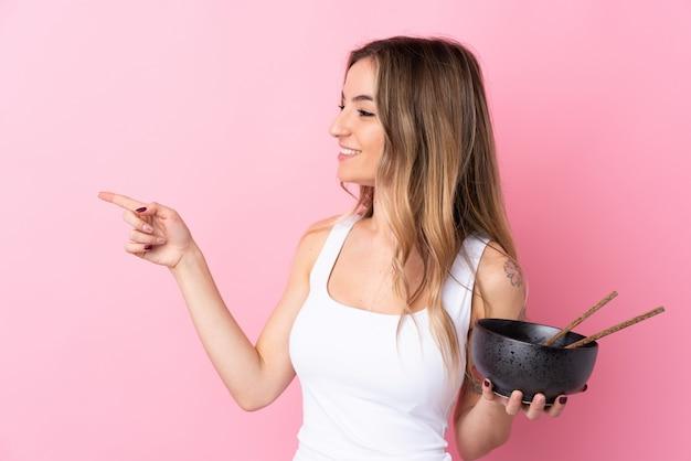 Jonge vrouw over geïsoleerde roze muur die aan de kant richt om een product te presenteren terwijl het houden van een kom noedels met eetstokjes