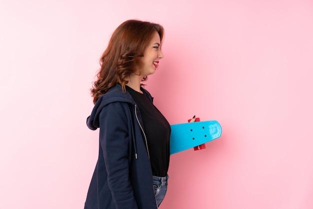 Jonge vrouw over geïsoleerde roze muur