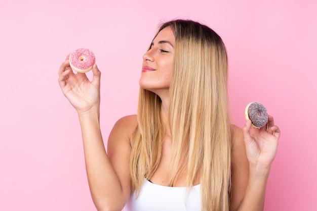 Jonge vrouw over geïsoleerde roze muurholding donuts met gelukkige uitdrukking