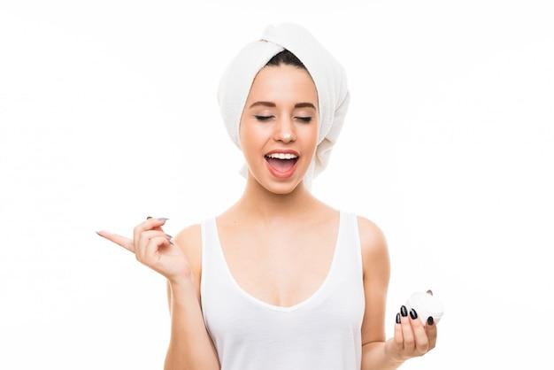 Jonge vrouw over geïsoleerde witte achtergrond met vochtinbrengende crème