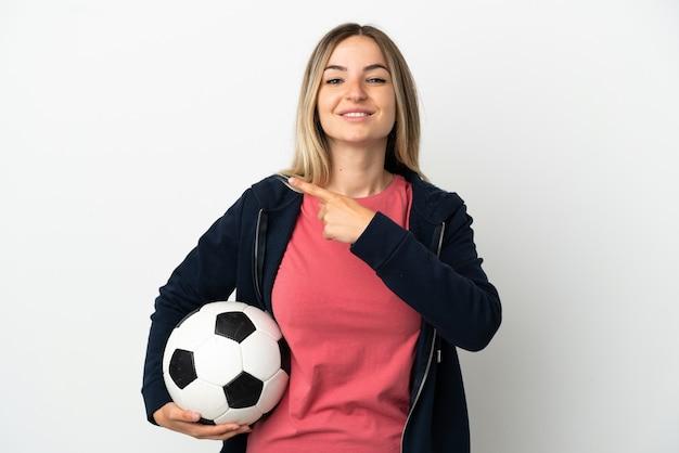 Jonge vrouw over geïsoleerde witte achtergrond met voetbal en wijzend naar de laterale