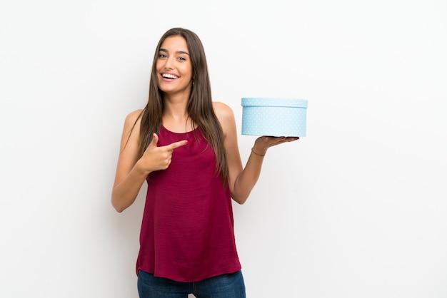 Jonge vrouw over geïsoleerde witte de giftdoos van de muurholding