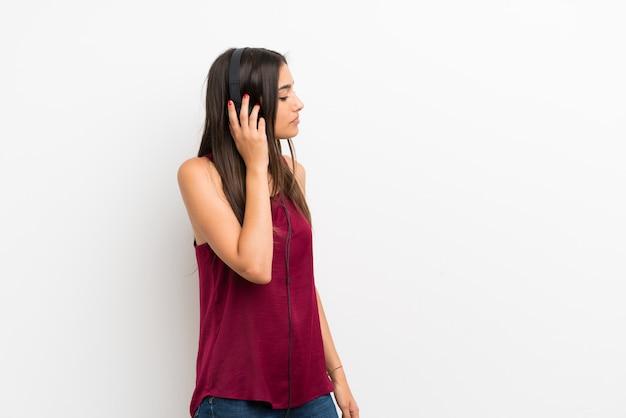 Jonge vrouw over geïsoleerde witte muur die aan muziek met hoofdtelefoons luistert