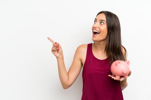 Jonge vrouw over geïsoleerde witte muur die een grote spaarpot houdt