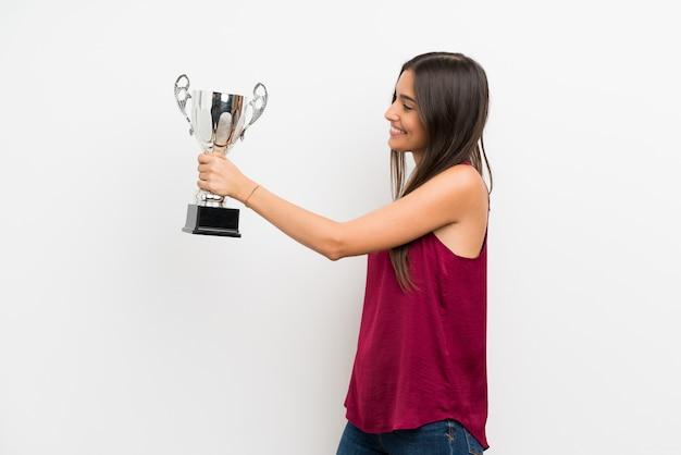 Jonge vrouw over geïsoleerde witte muur die een trofee houdt